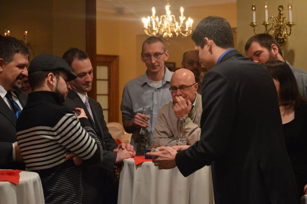 Audience watches in amazement as Magician Steven Brundage performs up-close magic at a private event